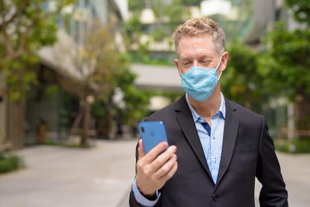 Uomo d'affari maturo che indossa la maschera utilizzando il telefono con la natura in città