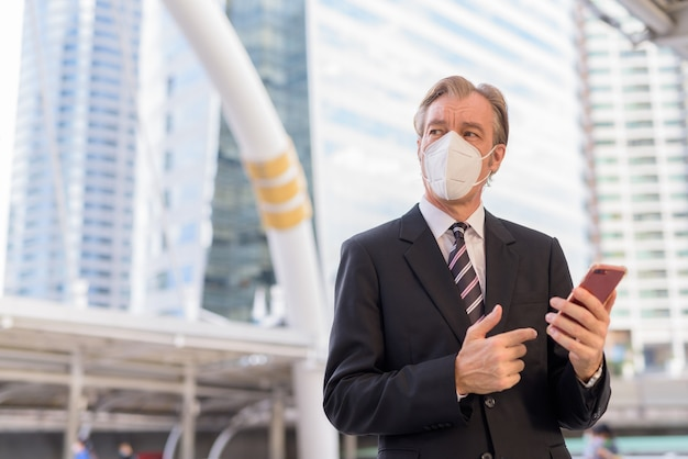 Imprenditore maturo con maschera pensando durante l'utilizzo del telefono a skywalk bridge