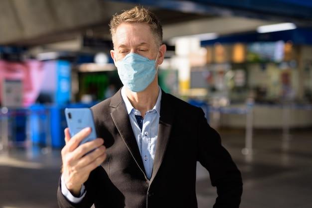 Uomo d'affari maturo con maschera utilizzando il telefono presso la stazione del treno del cielo