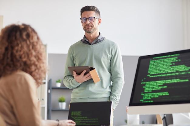 Uomo d'affari maturo con tablet pc discutendo presentazione online con il suo collega in ufficio