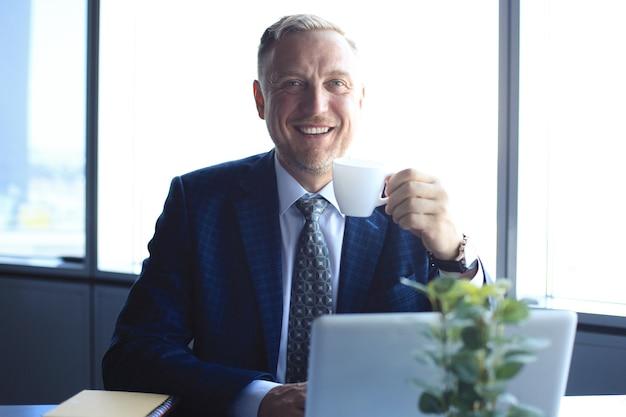 Uomo d'affari maturo che lavora al computer e beve caffè in un ufficio moderno.
