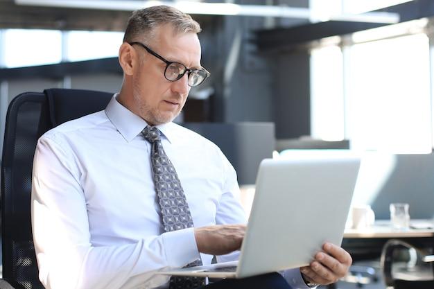 Uomo d'affari maturo che lavora al computer in un ufficio moderno.