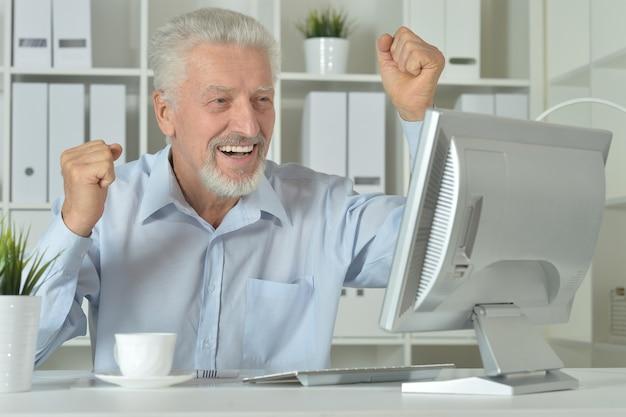 Uomo d'affari maturo che lavora con il computer portatile in ufficio