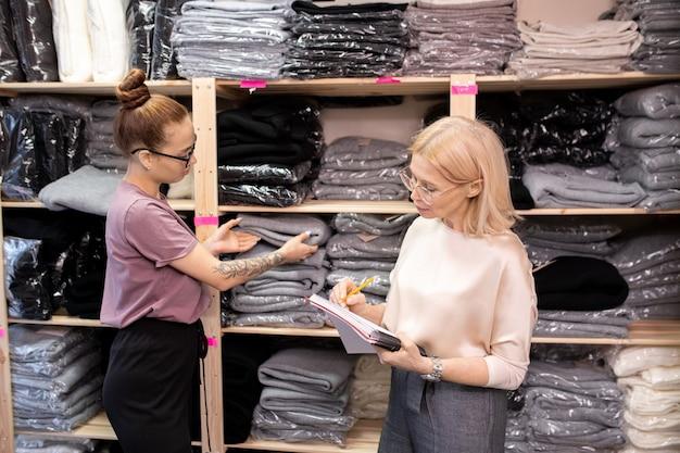 Donna d'affari matura che prende appunti in un documento con il suo assistente che controlla le cose sugli scaffali mentre lavorano in magazzino