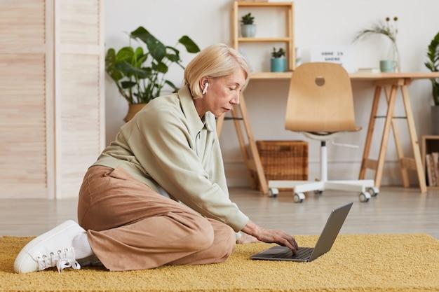 Coppia imprenditrice utilizzando il suo computer portatile mentre è seduto sul pavimento nel soggiorno