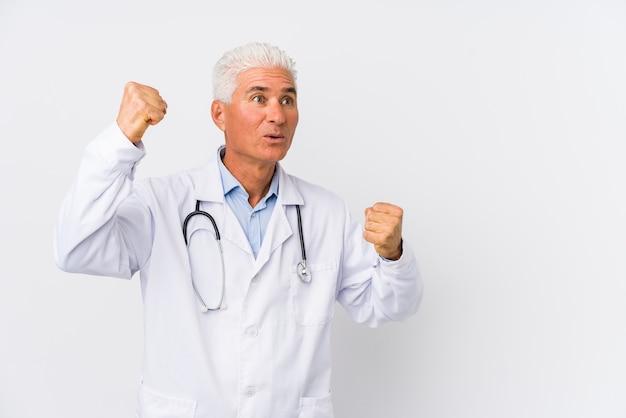 Uomo caucasico maturo del medico che alza il pugno dopo una vittoria, concetto del vincitore.