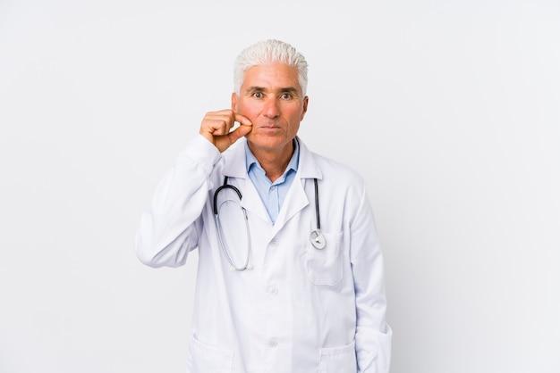 Uomo caucasico maturo di medico con le dita sulle labbra che tengono un segreto.