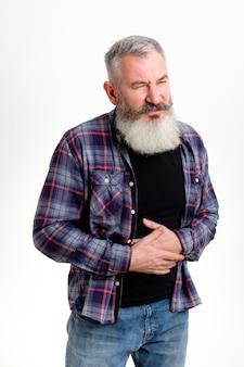 L'uomo caucasico maturo vestito con abiti casual si sente male, ha problemi di stomaco, malattie legate al cibo, intossicazioni acute, muro bianco