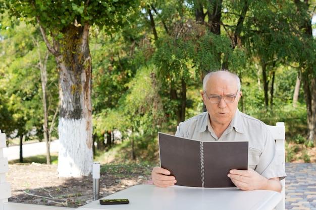Uomo caucasico maturo che legge il menu in un ristorante