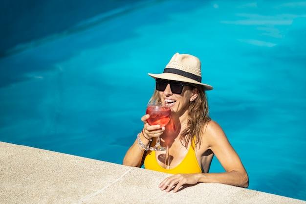 Matura donna caucasica bere cocktail in piscina. indossa cappello, occhiali da sole e costume da bagno giallo. sta bevendo un cocktail rosso in tazza. lei sta sorridendo