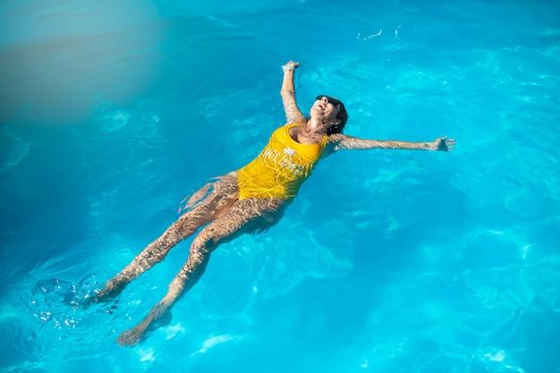 Donna caucasica matura che gode nella piscina blu. indossando occhiali da sole neri e costumi da bagno gialli