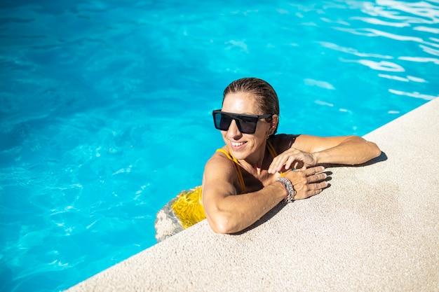 Donna caucasica matura che gode nella piscina. indossa occhiali da sole neri e costumi da bagno gialli