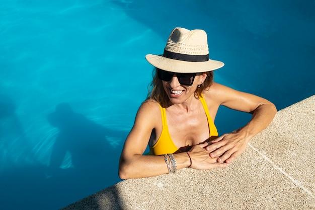 Donna caucasica matura che gode nella piscina. indossando occhiali da sole neri, costume da bagno giallo e cappello