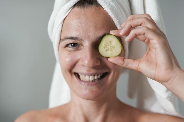 Donna caucasica matura che tiene una fetta di cetriolo fresco davanti al suo occhio - giornata di bellezza e concetto di cura della pelle