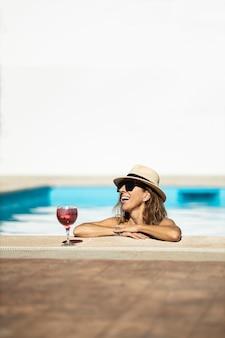 Donna caucasica matura che ride nella piscina. indossa cappello, occhiali da sole e costume da bagno giallo. è supportata a lato della piscina.
