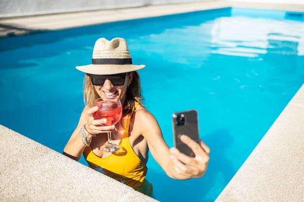 Donna caucasica matura che fa autoritratto in piscina con un telefono cellulare. indossa cappello, occhiali da sole e costume da bagno giallo. sta tenendo il cocktail rosso in tazza. lei sta sorridendo