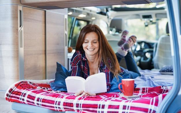 La donna caucasica matura si rilassa all'interno del mini van camper mentre legge un libro e beve caffè