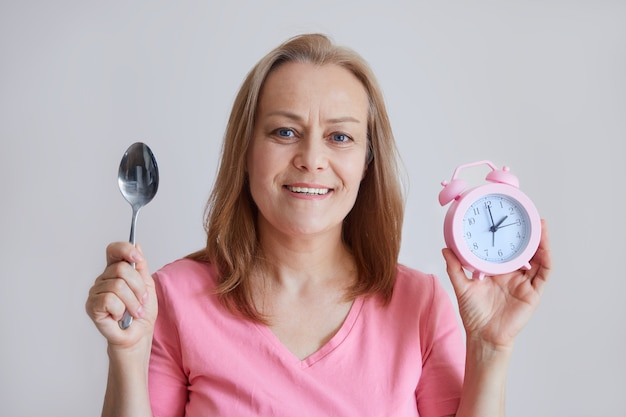 Una donna matura allegra tiene una sveglia in mano, un cucchiaio, guarda nella telecamera, ora di pranzo. foto su sfondo grigio.
