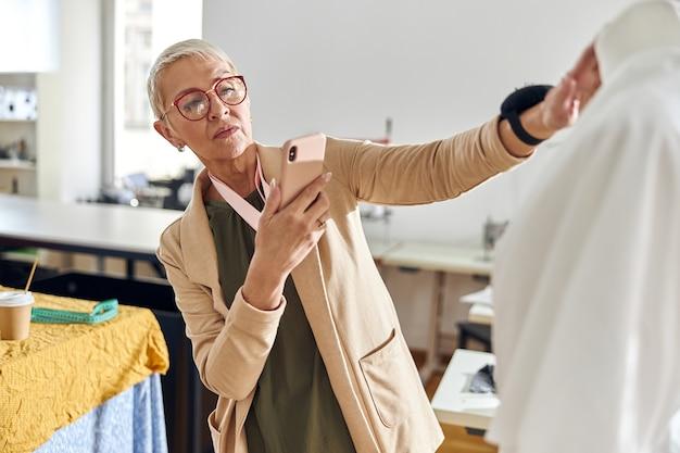 Il designer di abbigliamento maturo scatta la foto del nuovo modello di abbigliamento con il telefono cellulare nell'officina di cucito