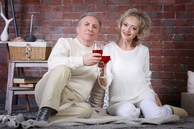 Coppia matura che beve vino insieme a casa