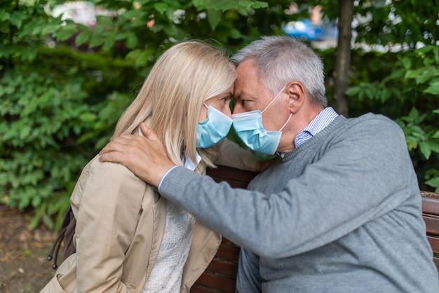 Coppie mature che abbracciano in un parco durante la pandemia di coronavirus