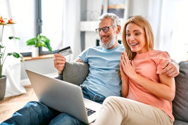 Una coppia matura è seduta sul divano a casa con un laptop e una carta di credito in mano.