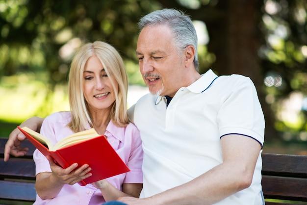 Coppia matura che legge un libro rosso nel parco