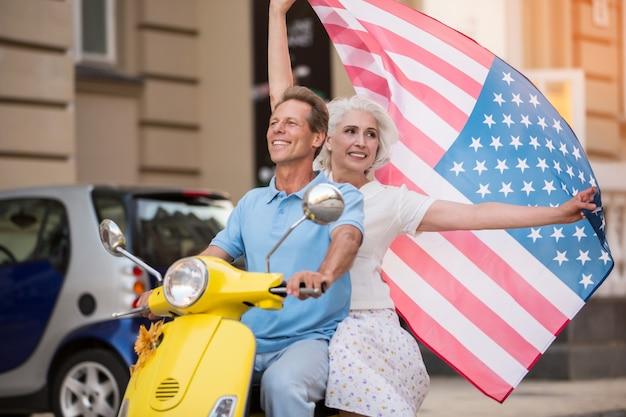 Coppia matura in sella a uno scooter giallo.