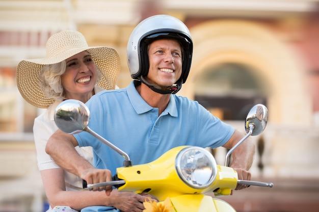 Coppia matura sui sorrisi di scooter.