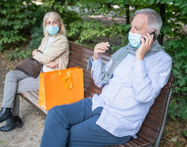 Coppia matura seduta ai lati di una panchina per mantenere le distanze durante i tempi del coronavirus