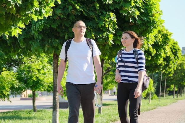 Coppia matura camminare e parlare di un uomo e di una donna, persone vestite in abiti sportivi che vanno all'allenamento fitness, stile di vita sano attivo e relazioni di persone di 40 anni