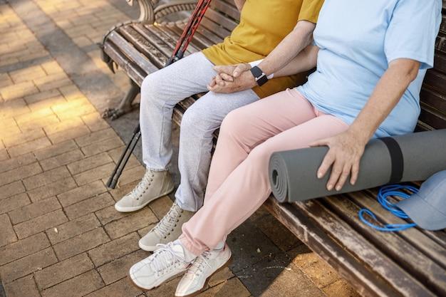 Una coppia matura con attrezzatura sportiva si unisce per mano seduta su una panchina nel primo piano del parco