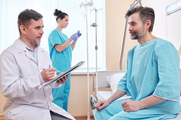 Medico maturo in camice da laboratorio, prendere appunti nella cartella clinica e parlare con il paziente in camice da ospedale durante la diagnosi