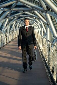 Maturo elegante delegato o uomo d'affari con borsa in pelle nera che si sposta lungo il corridoio davanti alla telecamera all'interno del business center