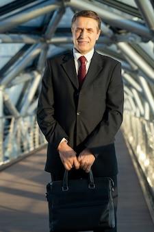 Maturo elegante delegato o uomo d'affari con borsa in pelle nera in piedi davanti alla telecamera all'interno del centro business contemporaneo