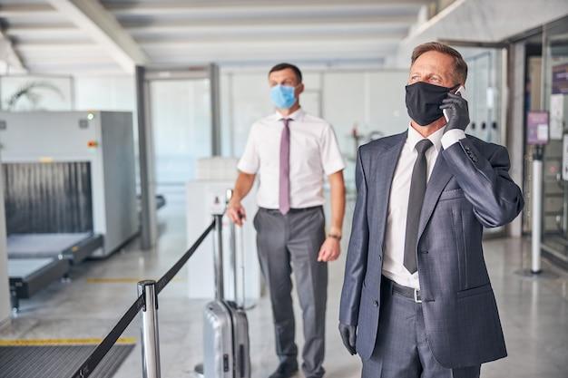 Il maschio elegante maturo in maschera sta facendo una chiamata mentre l'assistente sta trasportando i bagagli prima della partenza