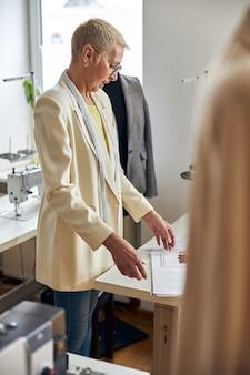 Lo stilista maturo con il metro a nastro prende i disegni dal tavolo nel laboratorio di cucito