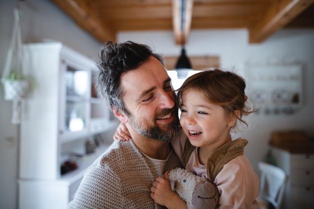 Padre maturo con figlia piccola in piedi in casa a casa tenendo e abbracciando