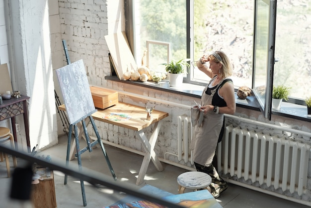Artista femminile maturo in grembiule stanco dopo la pittura asciugandosi il sudore dalla fronte e guardando l'immagine astratta