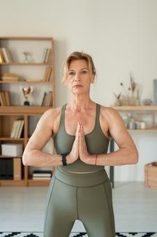 Sportiva in forma matura in tuta elastica grigia che si esercita con le mani sul petto mentre si tiene un corso di yoga contemporaneo a casa