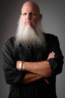Maturo bell'uomo calvo con una lunga barba bianca contro il muro grigio
