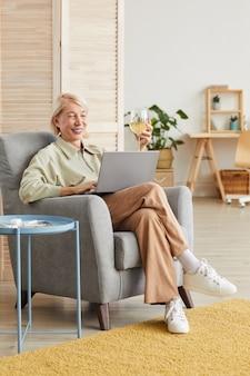 Coppia felice donna seduta sulla poltrona e digitando su un computer portatile nel soggiorno di casa