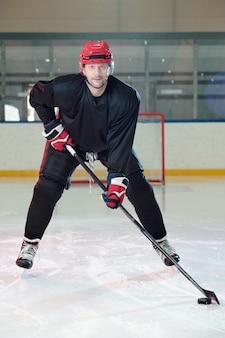 Giocatore di hockey maturo con casco protettivo e guanti che si spostano lungo la pista davanti alla telecamera e ti guardano mentre sparano al puck