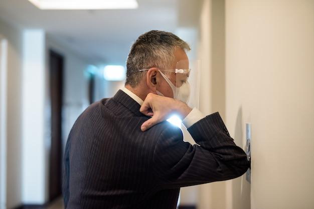 Maturo uomo d'affari giapponese con maschera e scudo viso premendo il pulsante dell'ascensore con il gomito