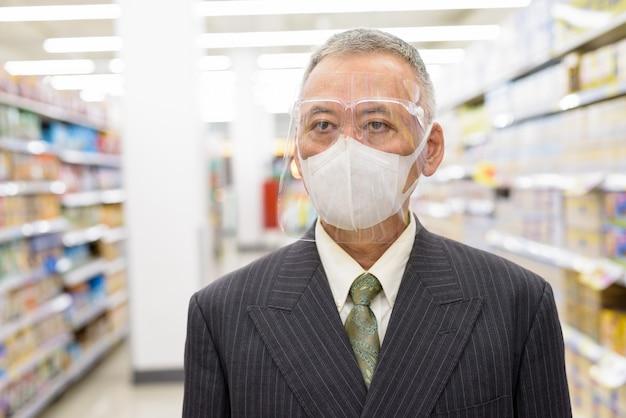 Uomo d'affari giapponese maturo con l'allontanamento sociale dello scudo facciale e della maschera al supermercato