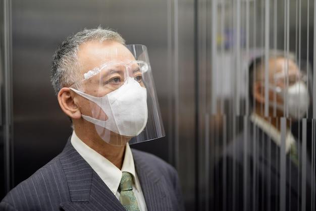 Uomo d'affari giapponese maturo con la maschera e la visiera che pensano dentro l'ascensore