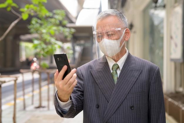 Uomo d'affari giapponese maturo con la maschera e la visiera facendo uso del telefono nella città