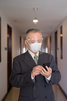 Uomo d'affari giapponese maturo con la maschera e la visiera facendo uso del telefono nel corridoio