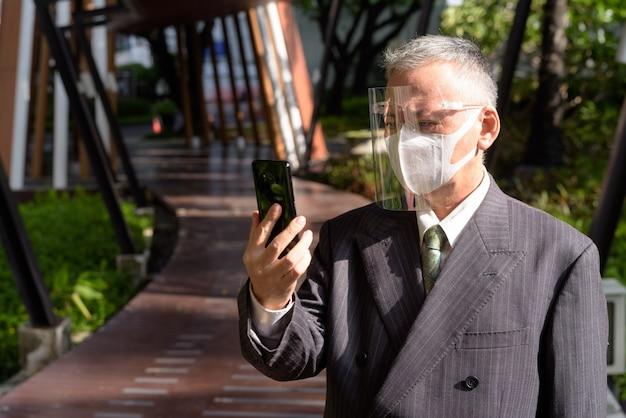 Uomo d'affari giapponese maturo con la maschera e la visiera facendo uso del telefono all'aperto
