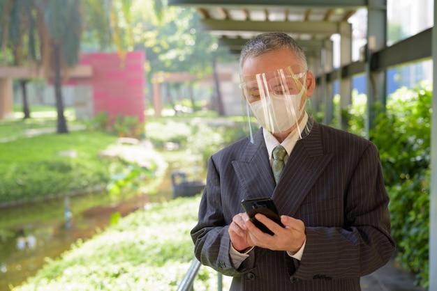 Uomo d'affari giapponese maturo con la maschera e la visiera facendo uso del telefono al parco